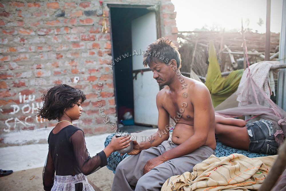 In the early morning, Poonam, 10, is offering some fresh water to her father, Suresh Jatev, 43, sitting on his wheeled cart next to his sleeping son Ravi, 12, (right) in the court yard of their newly built home in Oriya Basti, one of the water-contaminated colonies in Bhopal, central India, near the abandoned Union Carbide (now DOW Chemical) industrial complex, site of the infamous '1984 Gas Disaster'.