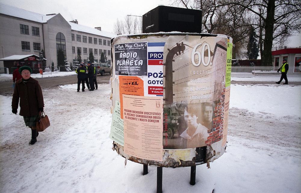 """Der Bahnhofvorplatz in der polnischen Stadt Oswiecim (Auschwitz). Oswiecim wurde zum Symbol für den unglaublichen und organisierten Massenmord durch die Nazis im 2. Weltkrieg. In Oswiecim befinden sich die Konzentrationslager """"Auschwitz 1"""" und """"Auschwitz 2 (Birkenau)"""". Auf dem Plakat ein Hinweis auf die Zeremonien in Auschwitz Birkenau, welche einen Tag vorher waren."""