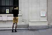 A lady smokes a cigarette outside the Bank of China in the City of London, Great Britain Uk