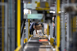 "© Licensed to London News Pictures . 04/12/2019. Manchester , UK . Packaged parcels move along a conveyor belt inside the ""MAN1"" Amazon fulfilment centre warehouse at Manchester Airport in the North West of England . Photo credit : Joel Goodman/LNP"