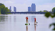 Video frame of SUP on the Grand River at Riverside Park in Grand Rapids, Michigan with skyscrapers of downtown Grand Rapids in the background.