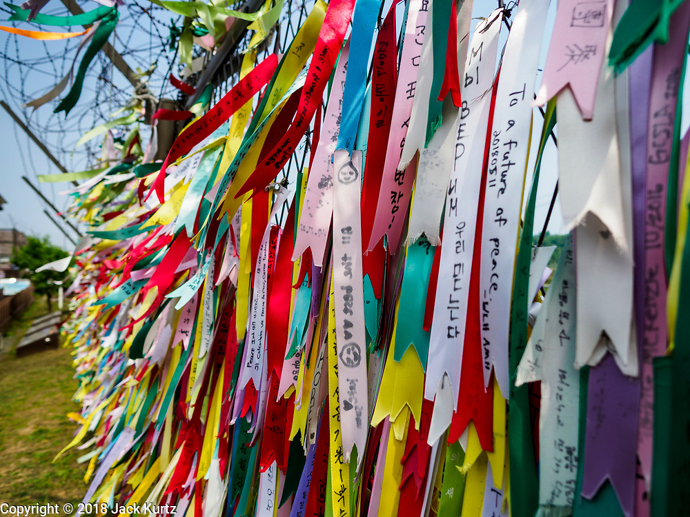 09 JUNE 2018 - IMJINGAK, PAJU, SOUTH KOREA: Prayer flags hang on fence near the northernmost point on the South Korean side of the Korean DMZ in Imjingak. The banners are left by visiting South Koreans and some tourists. Imjingak is a park and greenspace in South Korea that is farthest north most people can go without military authorization. The park is on the south bank of Imjin River, which separates South Korea from North Korea and is close the industrial park in Kaesong, North Korea that South and North Korea have jointly operated.     PHOTO BY JACK KURTZ