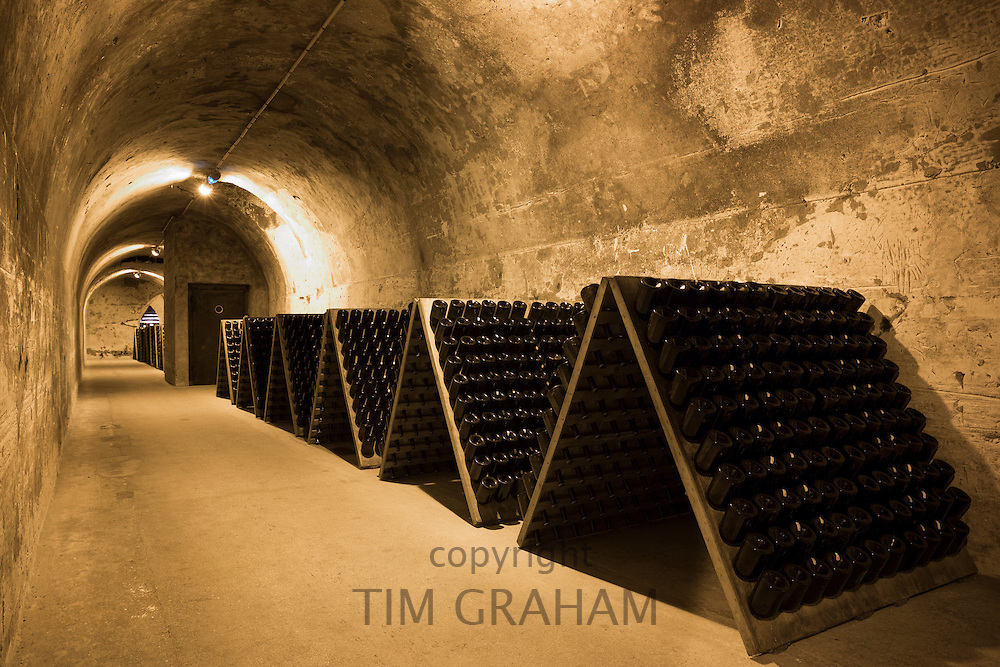 Methuselah bottles of champagne in frames for remuage in caves of Champagne Taittinger in Reims, Champagne-Ardenne, France