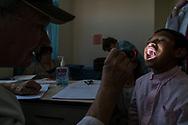 Central American Medical Outreach volunteer  doctor Lester Mohler examines Fernando Diaz Orellana, 11, during consultations at Occidente Hospital in Santa Rosa de Copan, Copan, Honduras on Feb. 19, 2017. Photo Ken Cedeno