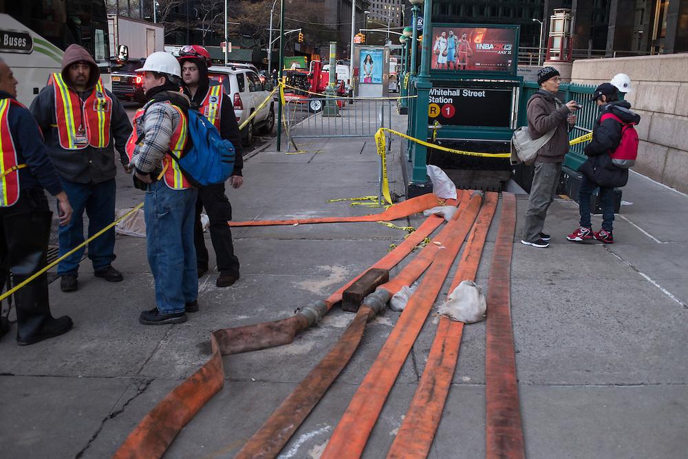 MTA workers take a break outside the Whitehall Street subway station. Orange drainage hoses snake across the sidewalk.