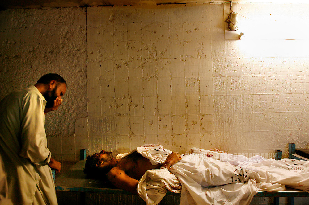 KARACHI, PAKISTAN - OCTOBER 19: A father weeps as he identifies the body of his son at the Ehdi morgue, October 19, 2007, Karachi, Pakistan. At least 140 people were killed in a suicide bombing aimed at assassinating former prime minister and opposition leader, Benazir Bhutto. Bhutto was unharmed in the Karachi blast, only to be gunned down two months later by an unknown assassin at an election rally in the garrison city of Rawalpindi on December 27. Bhutto returned to Pakistan after 7 years in self-imposed exile on a US-brokered power-sharing deal with President Musharraf. The deal collapsed after Musharraf implemented emergency rule in November, arresting and imprisoning thousands of opposition members and lawyers. During her short-lived campaign, Bhutto had vowed to restore civilian leadership and democracy, and crush Islamic militancy throughout the country. (Photo by Warrick Page)
