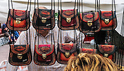 """Leather purses are sold at a San Telmo street fair, in Buenos Aires, Argentina, South America. Admire well-preserved old buildings in San Telmo (""""Saint Pedro González Telmo""""), the oldest barrio (neighborhood) of Buenos Aires."""
