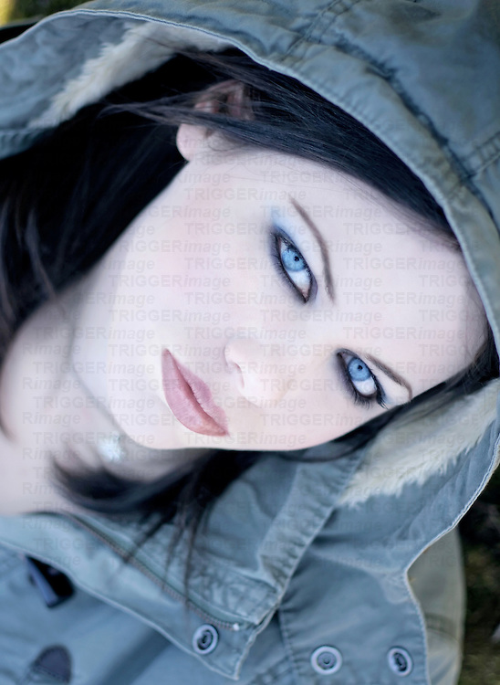 A sinister looking pale-skinned young woman with piercing blue eyes and a hooded coat
