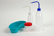 plastic bottles with distilled water and kidney dish for cleaning