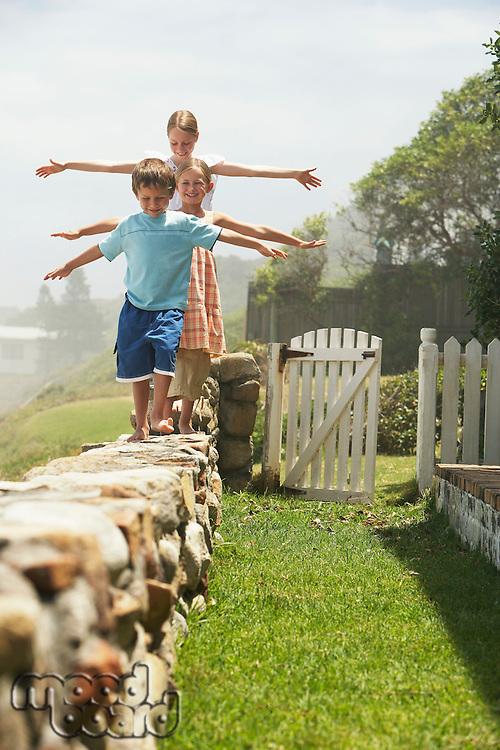 Three children (5-6 7-910-12) walking in row on stone wall