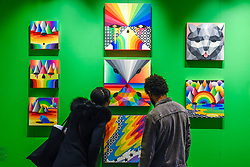 © Licensed to London News Pictures. 04/10/2019. LONDON, UK. Visitors view colourful works by Okuda San Miguel at Moniker International Art Fair, an urban contemporary art fair taking celebrating its 10 year anniversary in the UK.  The fair is  place at Chelsea's Sorting Office air until 6 October 2019.  Photo credit: Stephen Chung/LNP