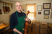 Boston violin maker Christopher White shows  a recently completed instrument, ready to be shipped to a customer.