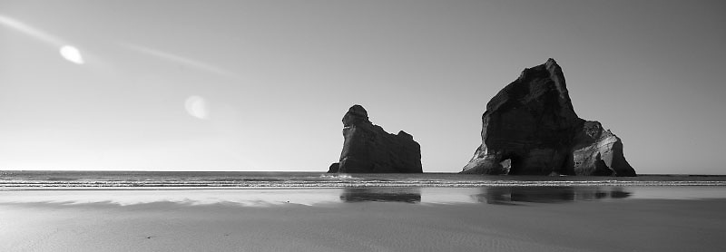 Two rock outcroppings stand alone on the beach.