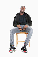 Portrait of a trendy African American man sitting on chair over gray background