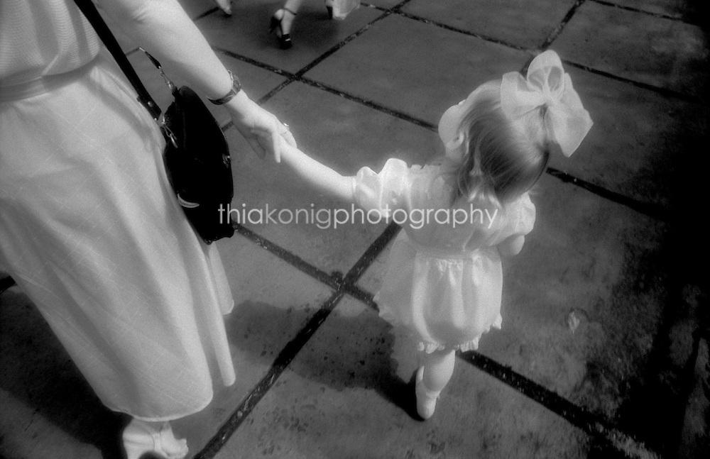 Little girl holding mother's hand while strolling in the park, Krasnoyarsk, Siberia.