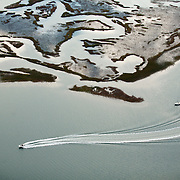 WRIGHTSVILLE BEACH, NC - Aerial photograph of a motor boat speeding between sailboats near marshes and barrier islands around Wrightsville Beach, NC