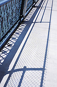 shadows from the guard rail on a bridge