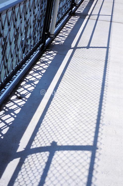 shadows from the guard rail on a bridge