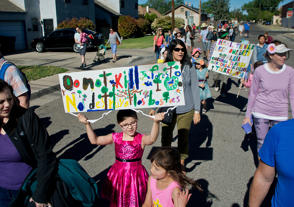 "mkb042117a/metro/Marla Brose --  Holding an Earth Day sign, Kaitlyn, an Escuela del Sol Montessori School student walks with family and friends during the school's annual Earth Day parade around the school's Albuquerque neighborhood, Friday, April 21, 2017. ""Even if you are small, you are mighty. Everyone can make a difference,"" said Elizabeth Marcilla, assistant head of school. About 300 people participated in the parade. (Marla Brose/Albuquerque Journal)"