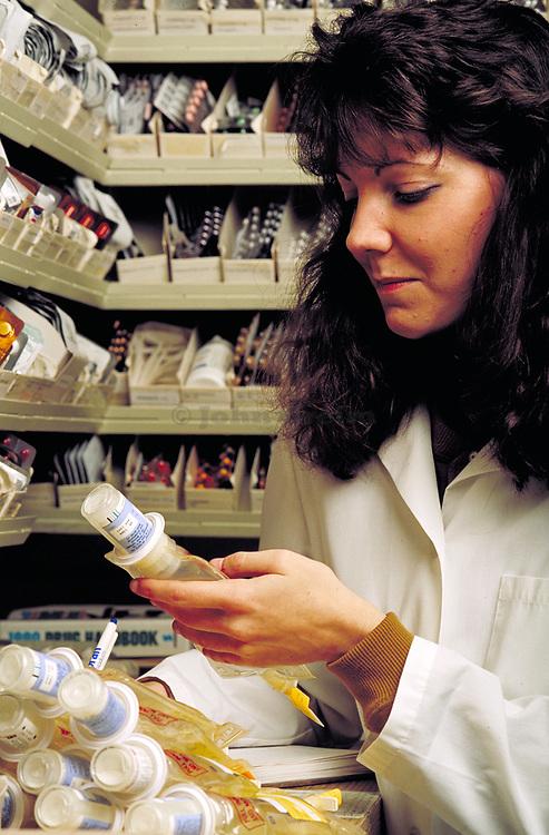 Pharmacist logging prescription drugs.