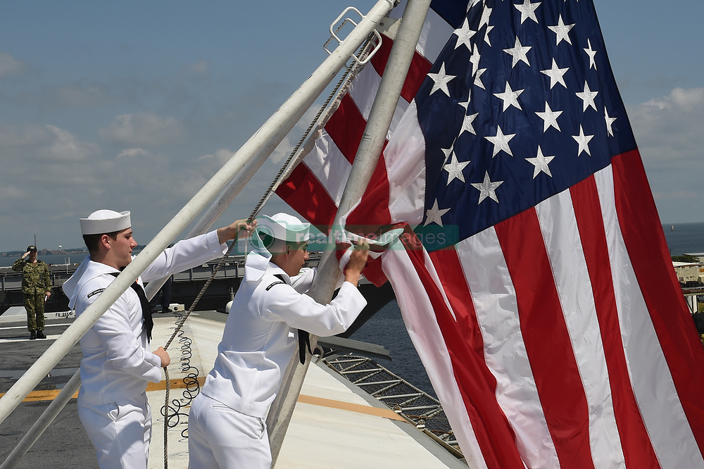 NORFOLK (Aug. 19, 2018) Aviation Ordnanceman 3rd Class Joseph Rodriguez, right, and Aviation Ordnanceman Airman Kevin Pawlowski lower the national ensign on the flight deck of the Nimitz-class aircraft carrier USS Abraham Lincoln (CVN 72). Abraham Lincoln is currently underway conducting carrier qualifications in preparation for an upcoming deployment. (U.S. Navy photo by Mass Communication Specialist 2nd Class Mark Andrew Hays/Released) 180819-N-JX484-008