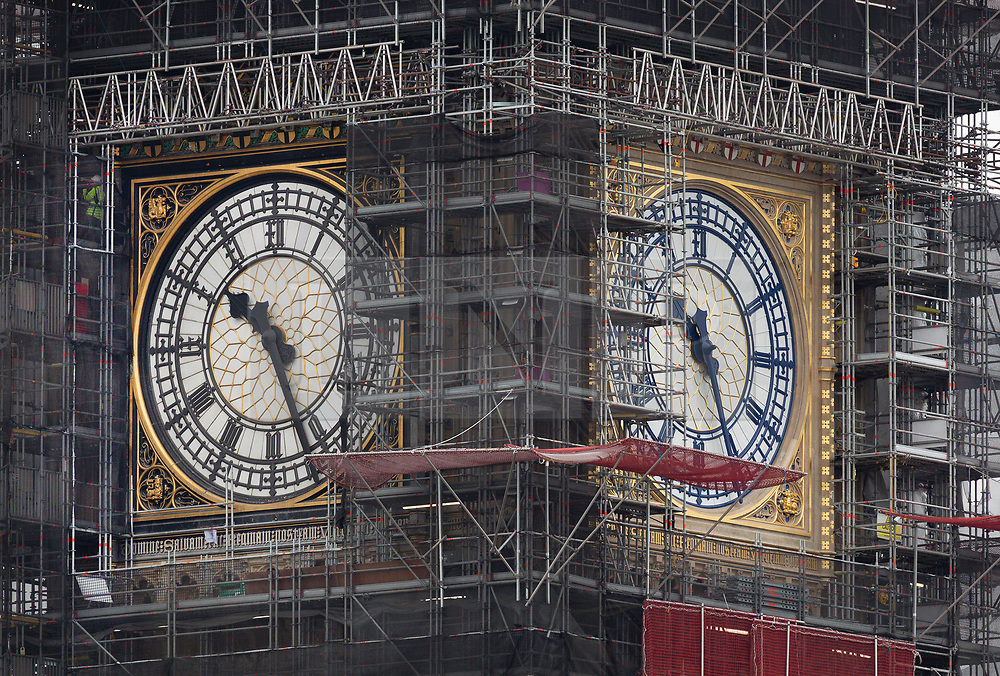© Licensed to London News Pictures. 20/03/2019. London, UK. One of the Elizabeth Tower clock faces (R) is revealed in its new Prussian Blue colour replacing the familiar black paint (L). Big Ben's north face is the first of the four famous clock faces to be seen in the original colour scheme from when it was built in 1859 by Sir Charles Barry. These works form part of a Parliamentary £61m restoration project which will also see the St George's shields at top of the clock face painted red and white for the first time since the 1930's.  Photo credit: Peter Macdiarmid/LNP
