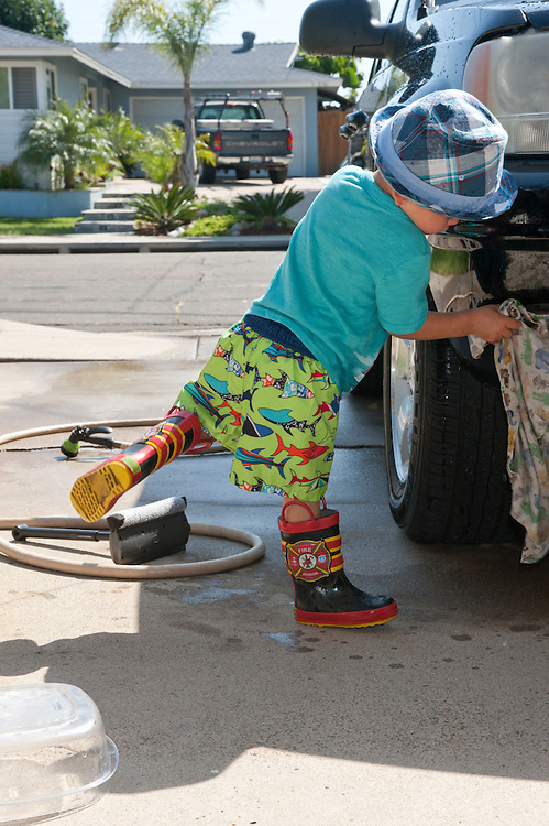 little boy in hat and rubber boots, one leg up in the air, hand-toweling his dad's car