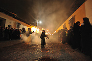 """Thick incense creates a haunting, ghost-like fog during """" Semana Santa"""" (Saints week) in Antigua, Guatemala. A passionate sensory experience that mingles Spanish and Mayan traditions in the week before Easter.  Crowds hush as the solemn procession passes by.  Colorful and festive """" emana Santa"""" (Saint week) in Antigua, Guatemala. A passionate sensory experience that mingles Spanish and Mayan traditions in the week before Easter.  ..The streets of Antigua, a UNESCO World Heritage site, are filled day and night with endless processions of people draped in robes, carrying massive coffins with effigies of  the crucified Jesus Christ.   luxurious alfombras (Arabic word for carpet) adorning the cobbled streets between processions.  Families and friends begin preparations weeks and months ahead of the festival to create these elaborate offerings.   The vibrant and intricately patterned carpets are made of dyed sawdust in hues of black, red, yellow, purple, blue, and green.  They are pressed through intricately designed cardboard stencils.  Flowers, seeds, plants, vegetables, and pine needles add the final touches to these temporary works of art.  The carpets' designs reflect biblical symbols, Mayan traditions, and scenes from nature.   The beautiful carpets are trampled by the processions, as a way to honor Christ's death and pay penance.h arrival at night. ..Spanish missionaries from Seville initiated this religious occasion during colonial times.  ...The floats weigh up to 7,000 pounds with 50-100 curcuruchas or carriers bearing their weight.  Funeral marching bands follow the floats, announcing themselves with sounds of slowly beating drums, clapping cymbals and deep-throated tubas. Thick incense creates a haunting, ghost-like fog. Crowds hush as the solemn procession passes by.  ..Antigua, a colonial town, is a UNESCO World Heritage site."""