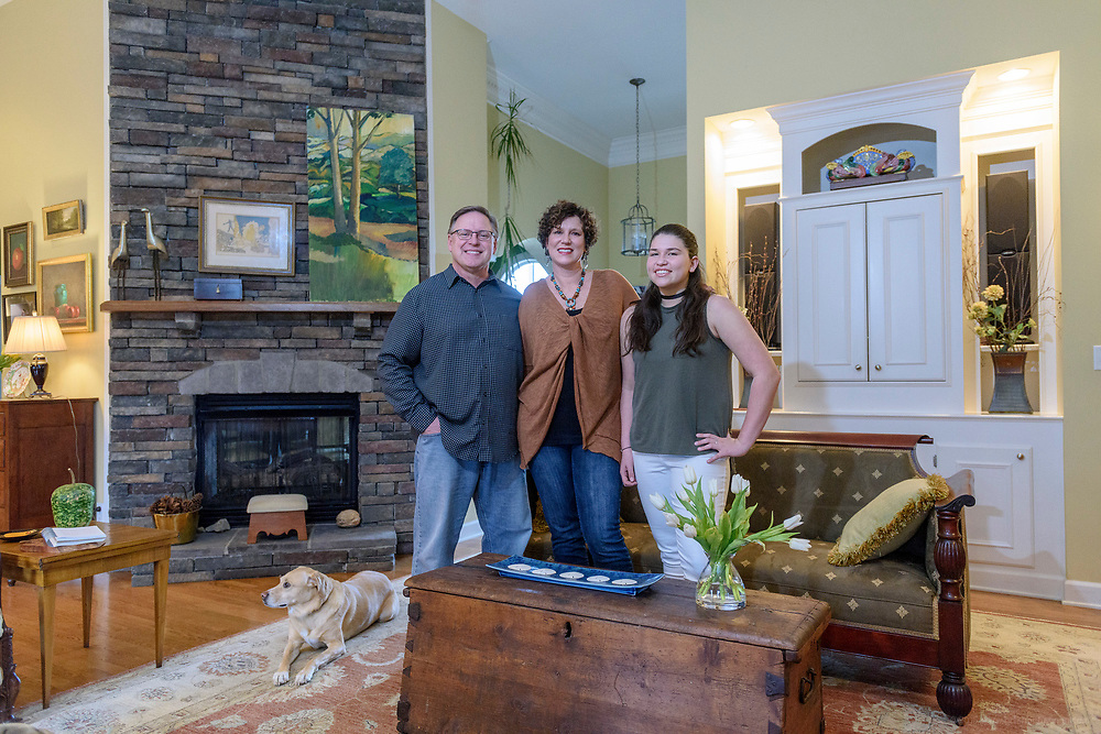 Kristen and David Embry with their daughter Gabby, 13, in the living room of their home in Pendleton, Ky. Cooper the Wonder Dog, 9, rests beside them. Feb. 22, 2018
