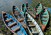 Colorful blue and green boats on Phewa Lake (or Fewa Tal), in Pokhara, Nepal.