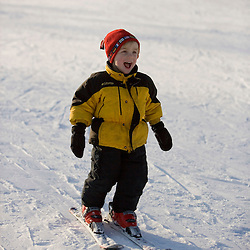 A young boy (age 3) learns to ski at the Quechee Ski Hill in Quechee, Vermont.