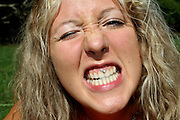 woman showing her white teeth and mouth piercing