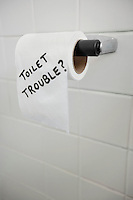 Close-up of text written on tissue paper in bathroom depicting toilet problems