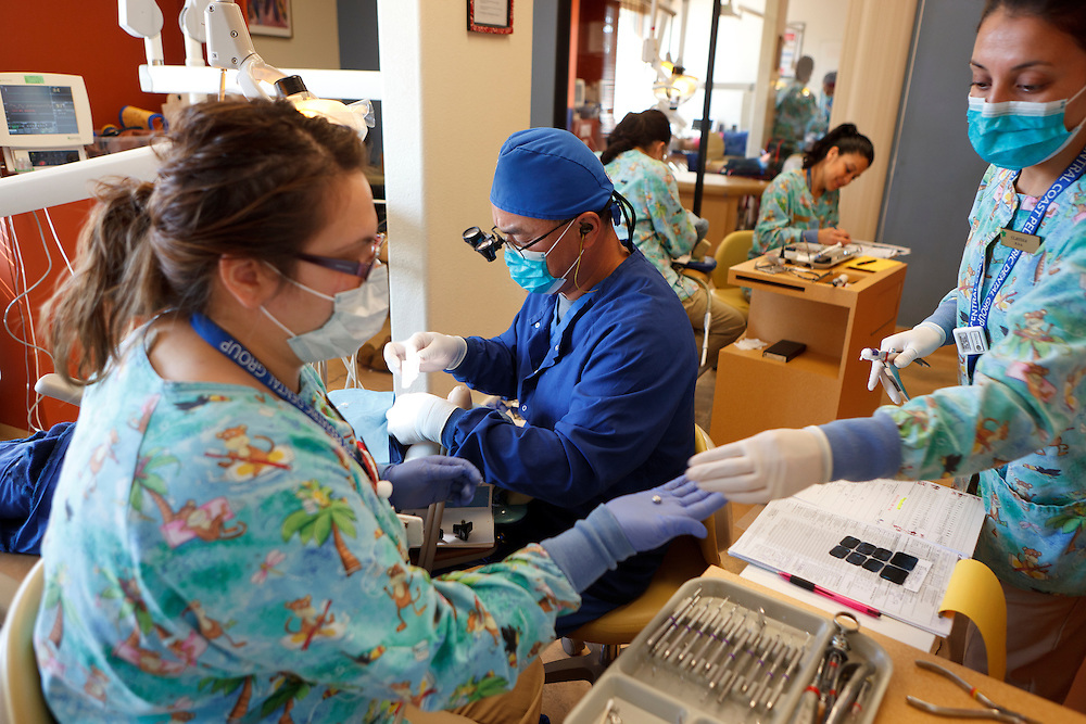 Peter Chiang, D.D.S., treats a patient Tuesday, Dec. 13, 2011, at Central Coast Pediatric Dental Group in Salinas, California. Cindy Lopez, R.D.A., is at left and Claudia Tinajero, R.D.A., is at right.