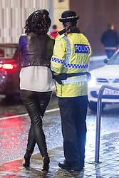 """© Licensed to London News Pictures . 20/12/2014 . Manchester , UK . A police officer guides a woman away from the city centre . """" Mad Friday """" revellers out in the rain and cold in Manchester . Mad Friday is typically the busiest day of the year for emergency services , taking place on the last Friday before Christmas when office Christmas parties and Christmas revellers enjoy a night out .  Photo credit : Joel Goodman/LNP"""
