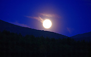 Full moon rising above the green mountains