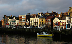 © Licensed to London News Pictures. <br /> 15/03/2015. <br /> <br /> Whitby, United Kingdom<br /> <br /> Morning sunlight reflects off houses and shop fronts in Whitby Harbour in North Yorkshire.<br /> <br /> Photo credit : Ian Forsyth/LNP