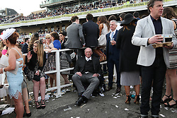 © Licensed to London News Pictures. 08/04/2016. Liverpool, UK. A man sits calmly among the drama on Ladies Day at the Grand National 2016 at Aintree Racecourse near Liverpool. The race, which was first run in 1839, is the most valuable jump race in Europe. Photo credit : Ian Hinchliffe/LNP