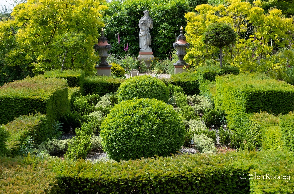 Stone urns and a 'Flora' statue in an area ofTaxus baccata and Buxus in the The Laskett Gardens, Much Birch, Herefordshire, UK
