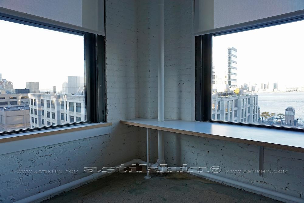 Empty white room corner with windows.