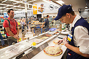 ROGERS, AR - OCTOBER 12:  Associate Jesse Shields makes a pizza for Brad Cardwell in the Deli Department at Walmart Store #4208 on October 12, 2015 in Rogers, Arkansas.  <br /> CREDIT Wesley Hitt for Wall Street Journal<br /> WALSQUEEZE