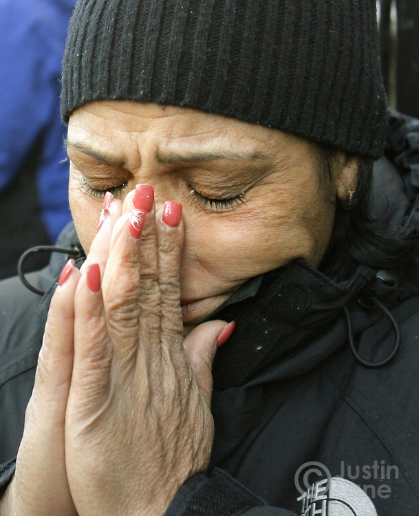 A woman, who lives in the neighborhood,  wipes away tears while standing outside of a house where 9 people were killed, 8 of them children, in a fire over night in the Bronx, New York on Thursday 08 March 2007.