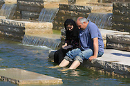 Woman in Islamic attire sits with man as they soak their feet in pond below the World's Fair Pavilion in Forest Park; St. Louis, Missouri.
