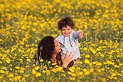 A two year old toddler with mother in a field of spring flowers