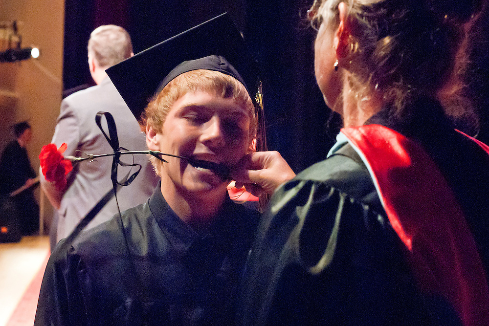 Lathan Goumas | MLive.com..A graduate takes a flower from a faculty member using his mouth during the LakeVille Memorial High School commencement ceremony at the Whiting Theater in Flint, Mich. on Wednesday June 6, 2012.