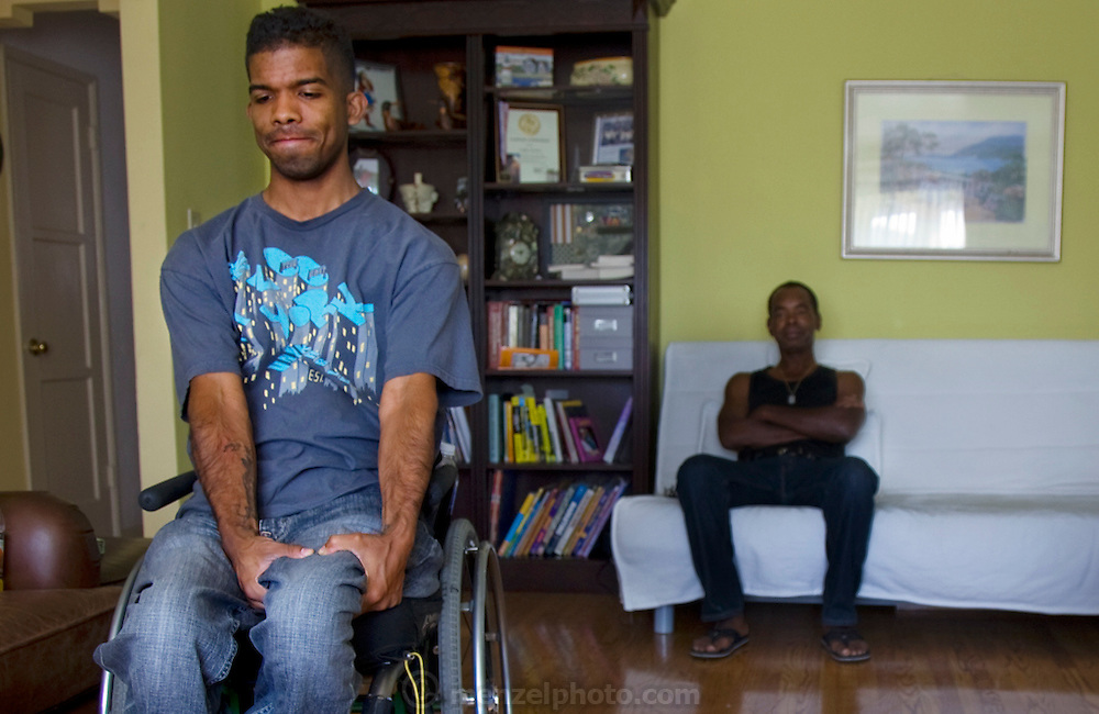 Felipe Adams, a 30-year-old Iraq war veteran, gripping his leg tightly as he experiences one of many episodes of phantom pain at his parents home in Inglewood, California. (From the book What I Eat: Around the World in 80 Diets.) The caloric value of his day's worth of food on a day in the month of September was 2100 kcals. He is 30 years of age; 5 feet, 10 inches tall; and 135 pounds. Felipe was paralyzed by a sniper's bullet in Baghdad, Iraq. Damaged nerves that normally enervate a missing or paralyzed body part can trigger the body's most basic warning that something isn't right: pain. Felipe experiences these phantom pains, which feel like stabbing electric shocks, dozens of times a day; they cause him to grip his leg tightly for a moment or two until the sensation subsides. MODEL RELEASED.