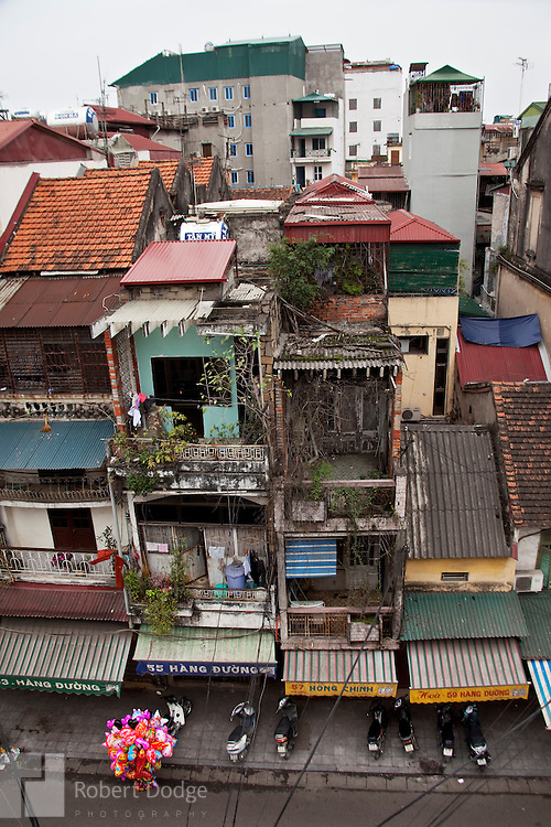 A balloon merchant makes his way up a Hanoi street. The balloons are popular gifts for children during Tet, the Lunar New Year. Hanoi's architecture of narrow but tall buildings are on full display. Robert Dodge, a Washington DC photographer and writer, has been working on his Vietnam 40 Years Later project since 2005. The project has taken him throughout Vietnam, including Hanoi, Ho Chi Minh City (Saigon), Nha Trang, Mue Nie, Phan Thiet, the Mekong, Sapa, Ninh Binh and the Perfume Pagoda. His images capture scenes and people from women in conical hats planting rice along the Red River in the north to men and women working in the floating markets one the Mekong River and its tributaries. Robert's project also captures the traditions of ancient Asia in the rural markets, Buddhist Monasteries and the celebrations around Tet, the Lunar New Year. Also to be found are images of the emerging modern Vietnam, such as young people eating and drinking and embracing the fashions and music of the west.
