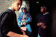 Group of bored teenage boys sitting in hallway of housing estate Lambeth Walk South London c.2000