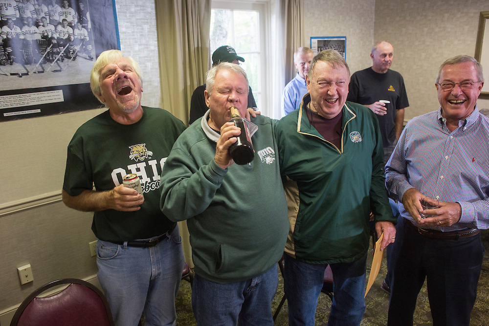 Bing Carlson takes a drink from a bottle of Purple Cow Cocktail while other hockey alumni watch and laugh during the 1960s hockey alumni reunion at the OU Inn on October 1, 2016.