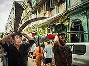 23 OCTOBER 2015 - YANGON, MYANMAR: Men carry huge lances on their heads during an Ashura procession going past Punja Mosque in Yangon. Ashura commemorates the death of Hussein ibn Ali, the grandson of the Prophet Muhammed, in the 7th century. Hussein ibn Ali is considered by Shia Muslims to be the third imam and the rightful successor of Muhammed. He was killed at the Battle of Karbala in 610 CE on the 10th day of Muharram, the first month of the Islamic calendar. According to Myanmar government statistics, only about 4% of the population is Muslim. Many Muslims have fled Myanmar in recent years because of violence directed against Burmese Muslims by Buddhist nationalists.    PHOTO BY JACK KURTZ
